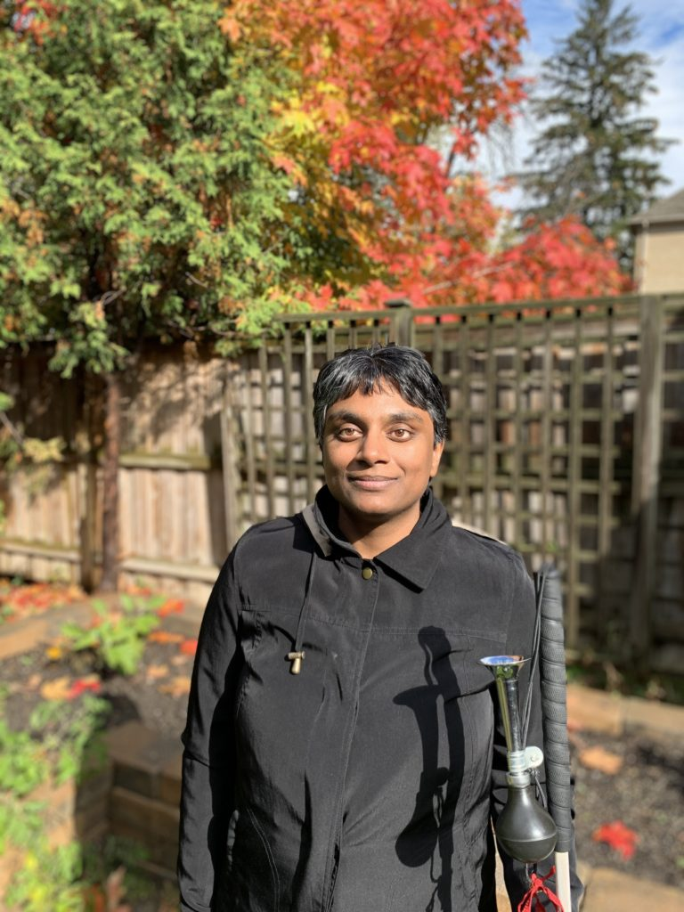 Nafisah is standing in the backyard at the CHKC Training Centre wearing a black jacket and holding her white cane. She is standing in front of a fence and maple tree that is changing colours.